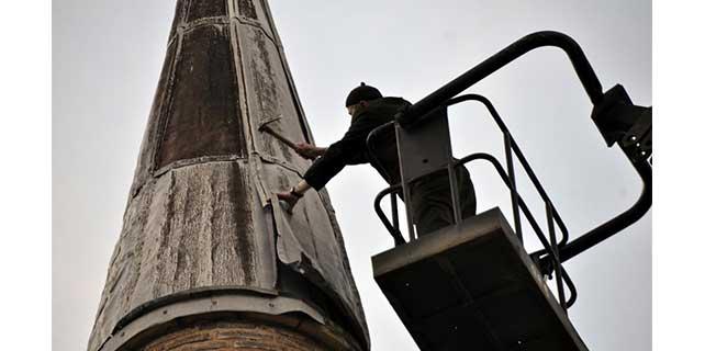 Cami minaresini vinç üzerinde tamir etti