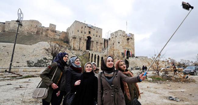 Şam'dan Halep'e gelen turistler yıkıntılar arasında poz verdi