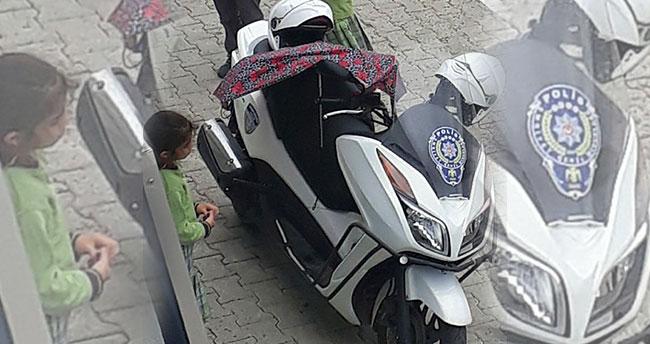 Polisin motosikleti ıslanmasın diye şemsiyeyle bekleyen küçük kız.